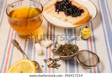 A cup of hot tea, a stainer with dry leaves, a slice of bread with berry jam on a wooden desk