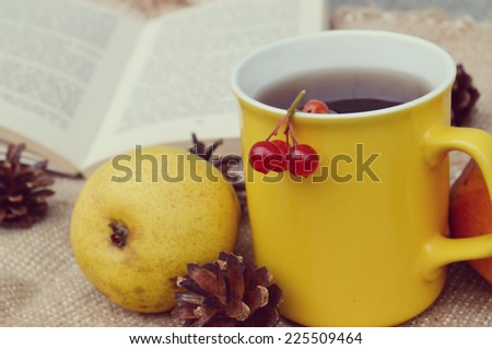 a Cup of hot tea , background of book ,  apples,autumn concept - stock photo