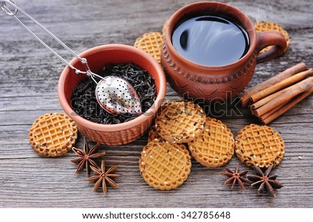 A cup of hot tea with cookies on a rustic wooden background - stock photo