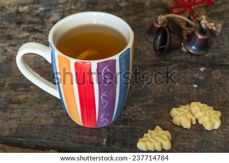 A cup of hot tea with lemon on rustic wooden table, close-up - stock photo