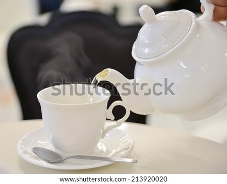 a cup of hot tea with white teapot