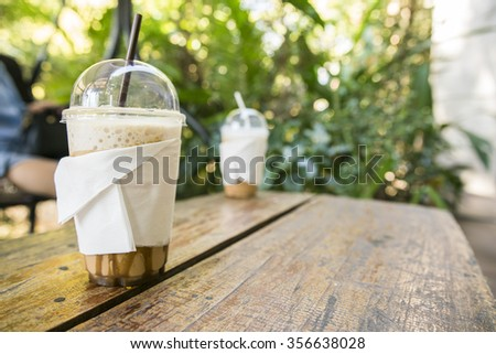 A 2 cup of Ice coffee on wooden table at coffee shop. - stock photo