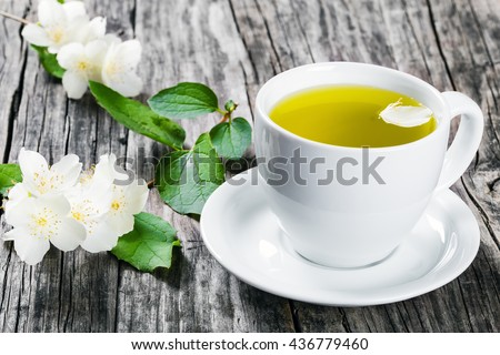 a cup of jasmine tea on a white saucer with flowers on dark wooden boards, close-up