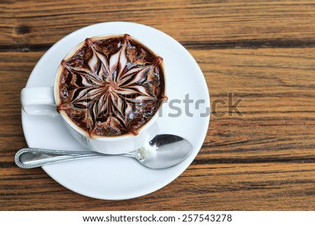 a cup of latte art hot coffee on wood table. - stock photo
