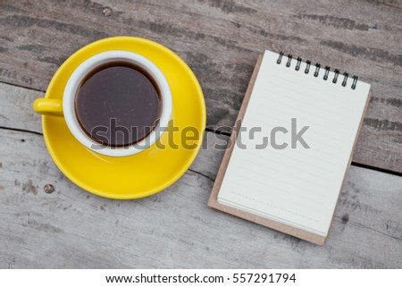A cup of lemon tea and notepad  on wooden table.