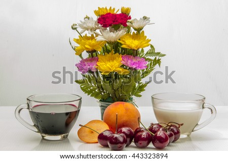 A cup of milk and a cup of grape juice with peach and cherry with whiten background - stock photo
