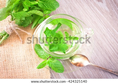 A cup of mint tea and a bunch of mint on the kitchen table - stock photo