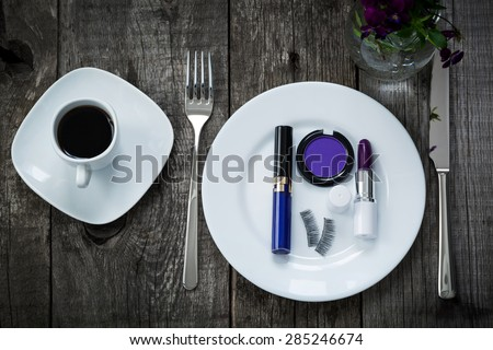 A cup of morning coffee,  lipstick, eyeshadow and fake eyelashes on plate on old wooden board, beauty concept of purple colors - stock photo