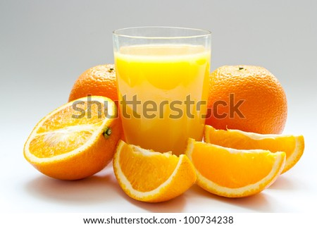 a cup of orange juice and fresh orange