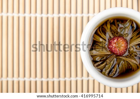 A cup of oriental flower tea on bamboo background  - stock photo