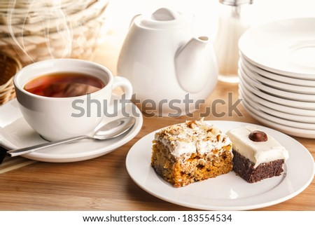 A cup of steaming tea with two pieces of cake on plate surrounded by various kitchenware on wooden plate.