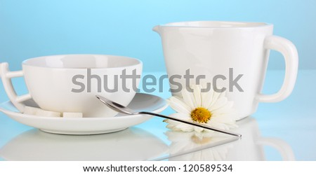 A cup of strong coffee and sweet cream on blue background - stock photo
