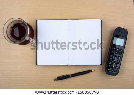 A cup of tea, an open notebook, a ballpoint pen and a black phone on wooden texture imitating an office desk. - stock photo