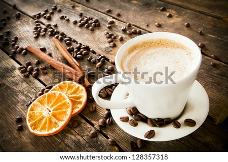 A cup of tea and biscuits and orange on the wooden table.