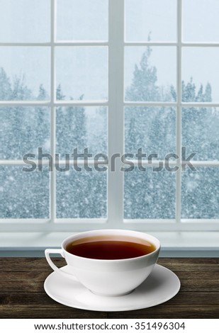 A cup of tea and snowstorm view from the window on the background - stock photo