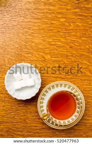 A cup of tea and sugar cubes from above.