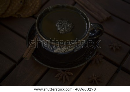 a cup of tea of glazed ceramics. On the saucer cinnamon stick and star anise. Three cookies on a table of dark wood - stock photo