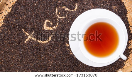 A cup of tea on dried and processed tea leaves with written TEA word