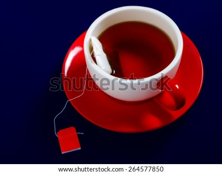 A cup of tea on red saucer in the dark blue background - stock photo