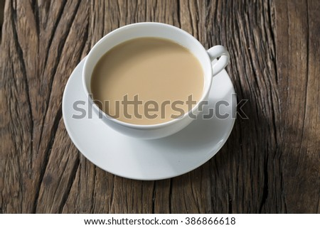 A cup of tea sitting on an old rustic wooden table. - stock photo