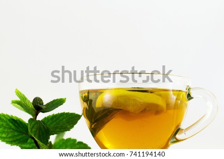 A cup of tea with lemon and mint. White background