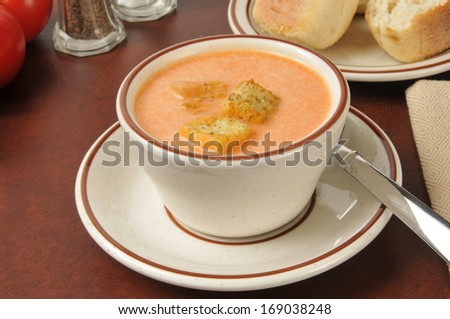 A cup of tomato bisque with croutons