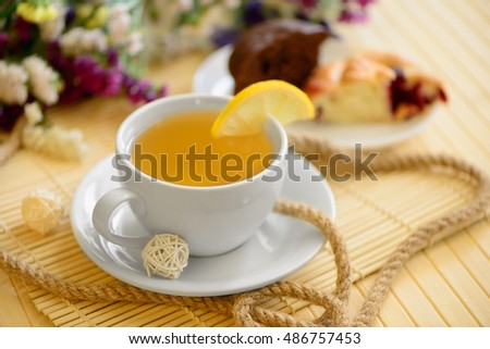 a cup of warm tea cakes and spring flowers