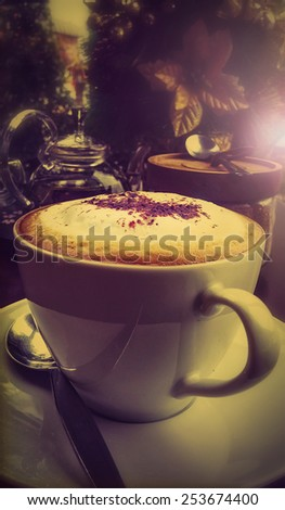 A cup ofCappuccino with dark retro style coffee shop background memory under light classica tea in a glass of water background - stock photo