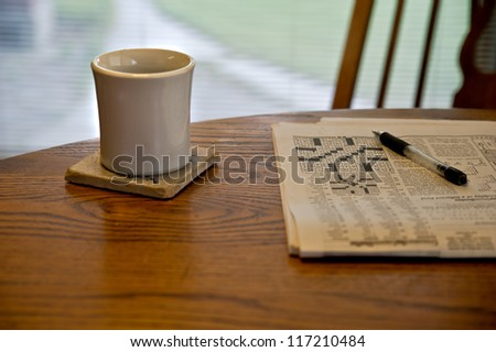 A cup sits on a coaster on a dining table alongside a partially completed crossword puzzle, part of a morning routine.  The table sits in front of a north facing window