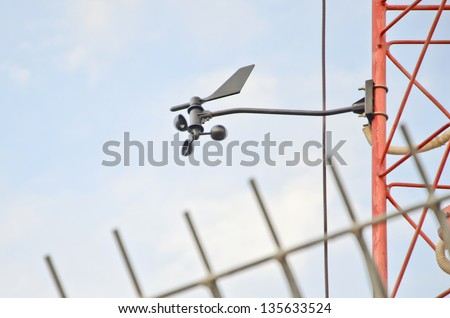 A cup-type anemometer measures the wind speed on blue sky - stock photo