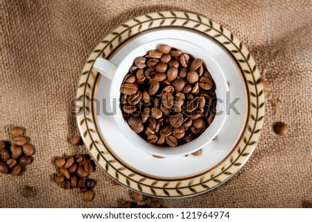 a cup wit coffee beans on the sack