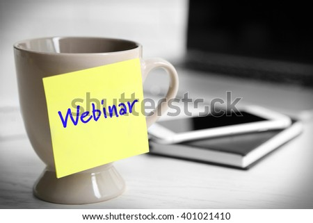 A cup with sticky note on the office table, close up. Webinar concept - stock photo