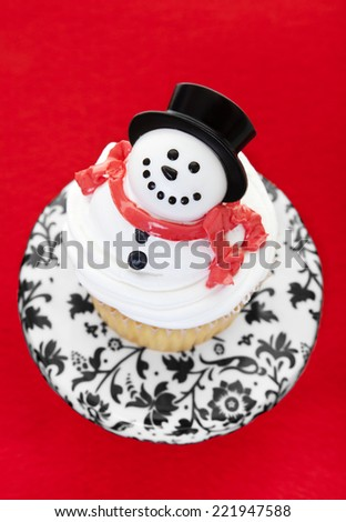 A cupcake decorated as a snowman on a cupcake pedestal.