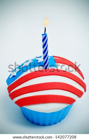a cupcake, decorated with the colors and stars of the flag of the United States, with a lit candle - stock photo