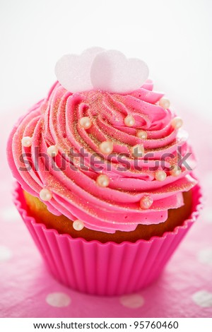 A cupcake in a pink baking cups with pink cream, white decoration and two hearts on the top on pink background as a studio shoot
