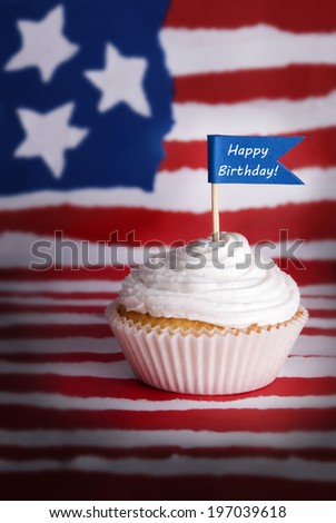 A Cupcake with a Happy Birthday Flag in it, on an American Flag Background - stock photo