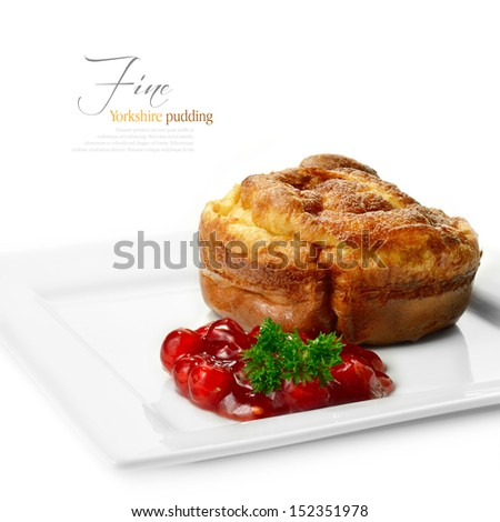 A curated image from my FINE series set. Macro image of a Yorkshire pudding with redcurrant jelly against a white background. My late father's recipe, passed down. Copy space. - stock photo