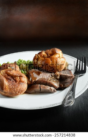 A curated image of topside roast beef, roast potatoes and traditional Yorkshire pudding in a restaurant setting against a dark background with copy space. Concept image for a Sunday lunch menu design. - stock photo