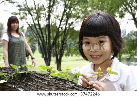 A curious Asian girl examining a creeper plant as her mother watches