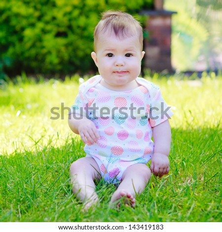 A curious baby in a vest sitting on a grass