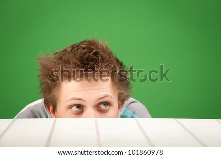 a curious teenager student looks up from the table in the classroom - stock photo