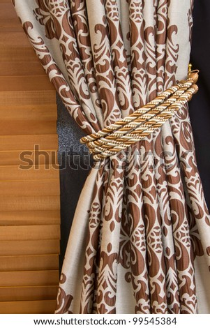 A curtain hold back by tassel - stock photo