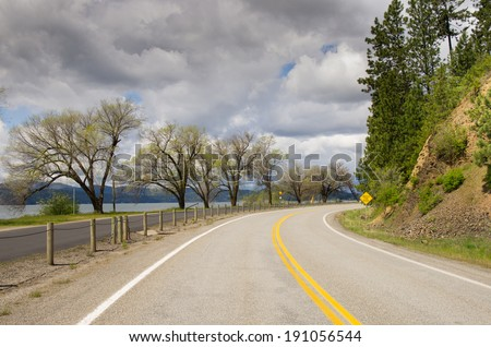 A curve in a lakeside road on a stormy day - stock photo