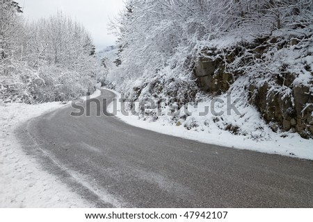 A curve in an empty, icy road through the mountains during winter - stock photo