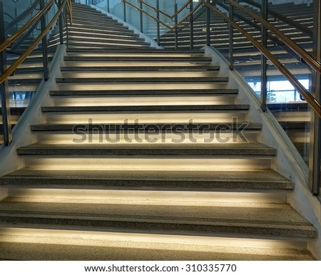A curved staircase with illuminated stairs and banisters - stock photo