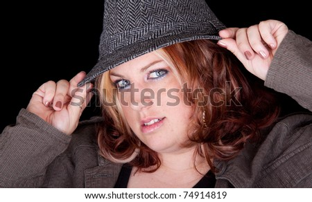A curvy gal fixes her hat and looks at the viewer.