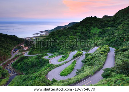 A curvy road through the grassy hills with a view of the ocean. - stock photo