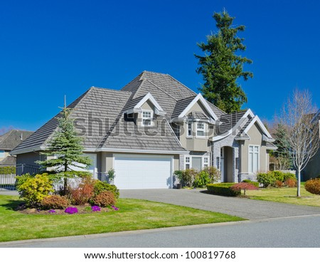 A custom built luxury house with the triple garage doors in a residential neighborhood. This high end home is very nicely landscaped property. - stock photo