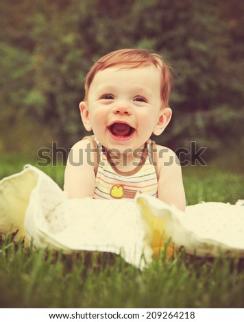a cut boy laughing on a blanket outside toned with a retro vintage instagram filter  - stock photo