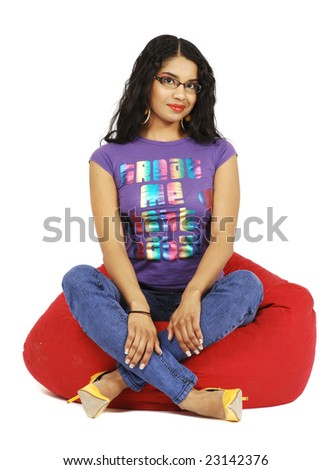 A cute African American girl sitting on a red beanbag chair. - stock photo
